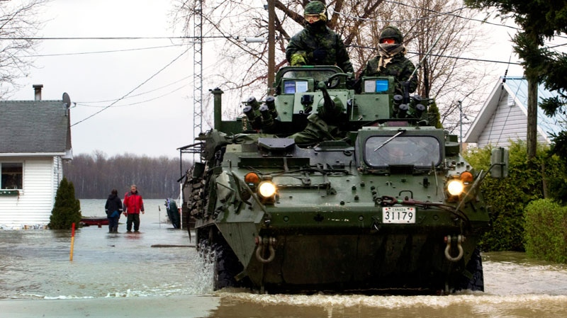 Soldiers from the 22nd Regiment, known as the VanDoos, drive their light armoured vehicle through the flooded streets of Saint Blaise, Que., Thursday, May 5, 2011. (yan Remiorz / THE CANADIAN PRESS/)