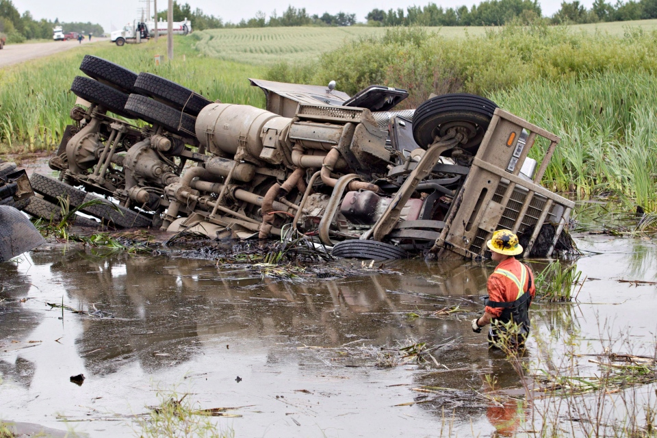 Crews work to pull a semi out of a pond that was involved in a collision with another vehicle near Lloydminster, Sask., on Saturday, July 27, 2013. (Jason Franson / THE CANADIAN PRESS)