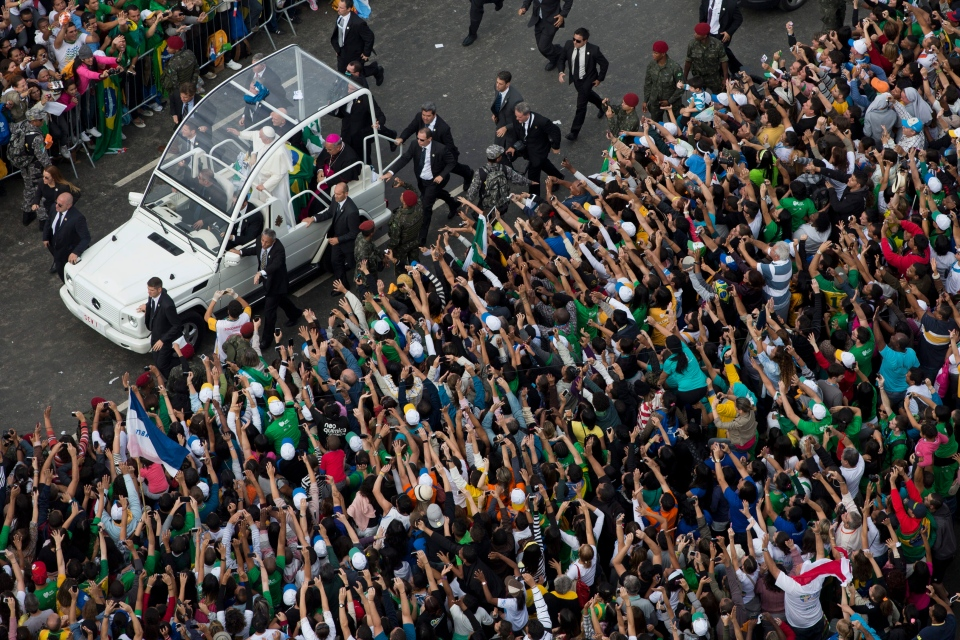 Pope Francis waves from the popemobile as he rides along the Copacabana beachfront on his way to celebrate mass in Rio de Janeiro Sunday July 28, 2013. (AP / Felipe Dana)