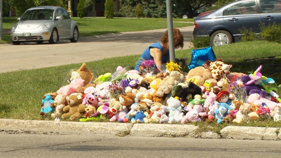 A neighbour leaves a small toy at a memorial for two children and their mother in Winnipeg, Sunday, July 28, 2013.