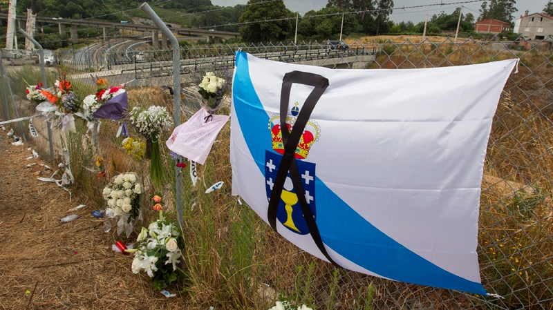 Bouquets and a Galician type flag with a black ribbon signaling mourning are seen by the train crash site in Santiago de Compostela, Spain, Sunday July 28, 2013. (AP / Lalo R. Villar)
