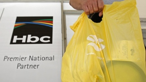 A man carries a bag with his purchases as he leaves The Bay department store in downtown Vancouver, B.C., on Wednesday, July 16, 2008. (Darryl Dyck / THE CANADIAN PRESS)