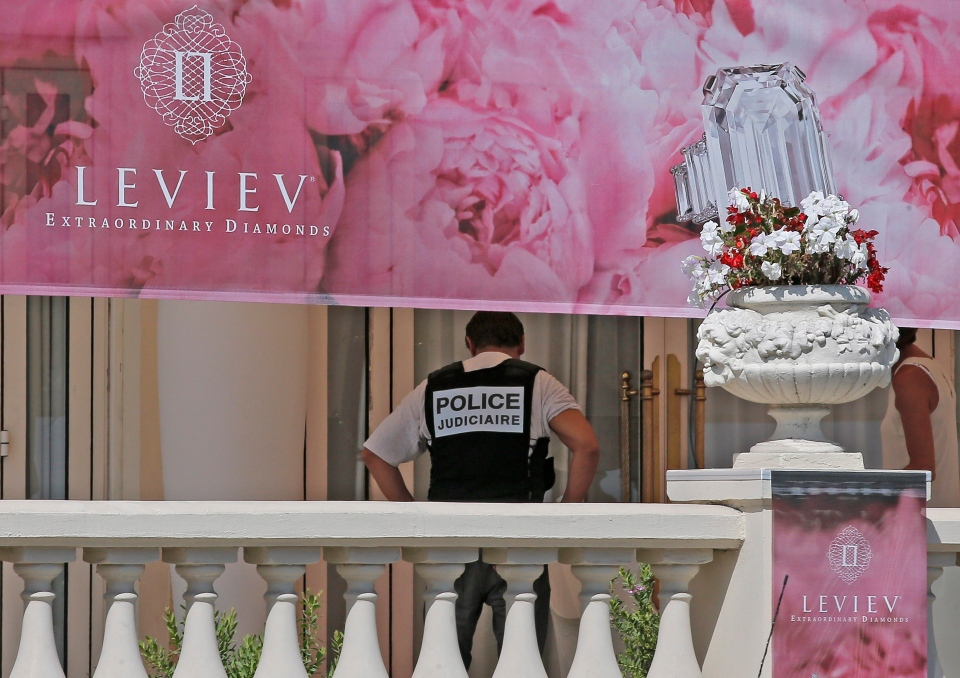 A policeman is seen at the Carlton hotel, in Cannes, southern France, the scene of a daylight raid, Sunday, July 28, 2013. (AP / Lionel Cironneau)