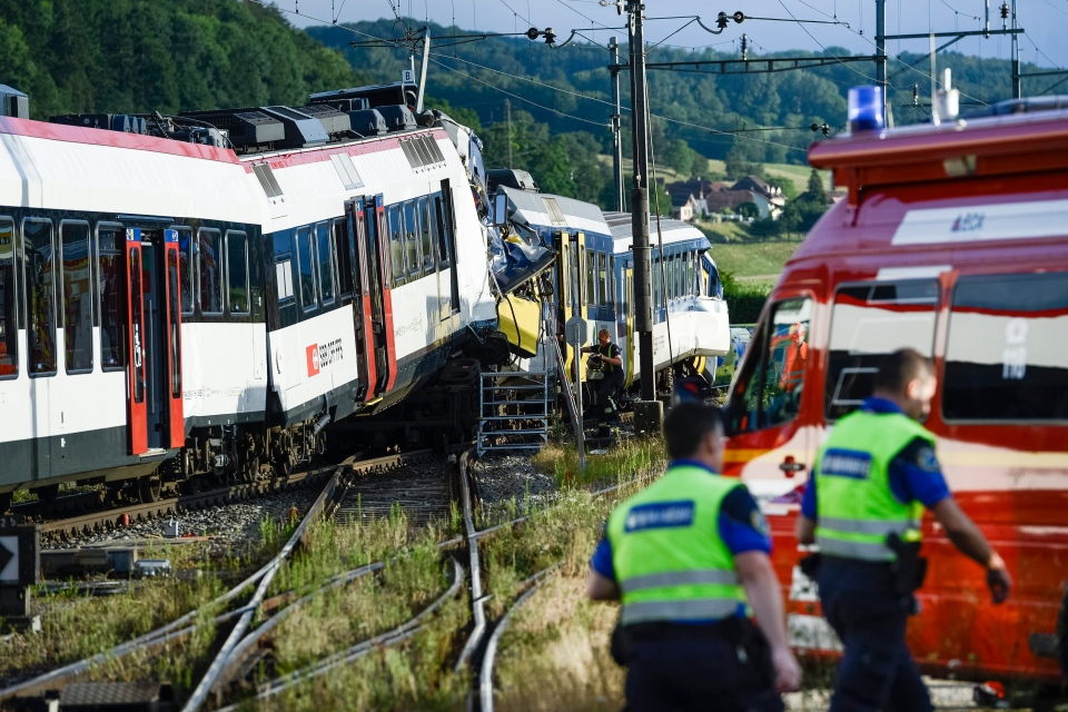 Rescue personnel work at the site where two passenger trains collided head-on in Granges-pres-Marnand, western Switzerland, Monday, July 29, 2013. (AP / Keystone, Laurent Gillieron)
