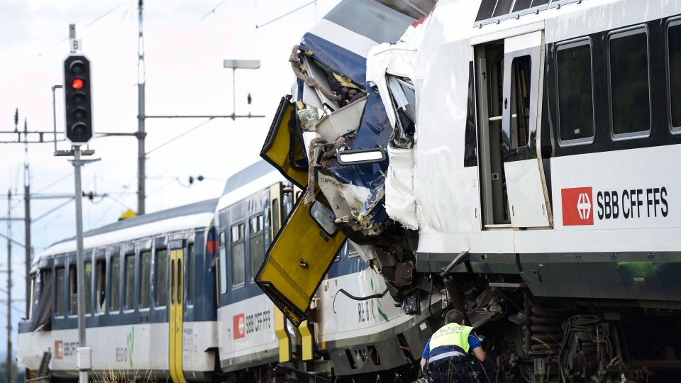 A signal shows red light as a police officer works at the site where two passenger trains collided head-on in Granges-pres-Marnand, western Switzerland, Monday, July 29, 2013. (AP / Keystone, Laurent Gillieron)