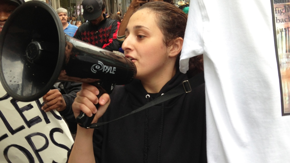 Sammy Yatim's sister holds a microphone at a vigil in Yonge-Dundas Square in Toronto on Monday, July 29, 2013.