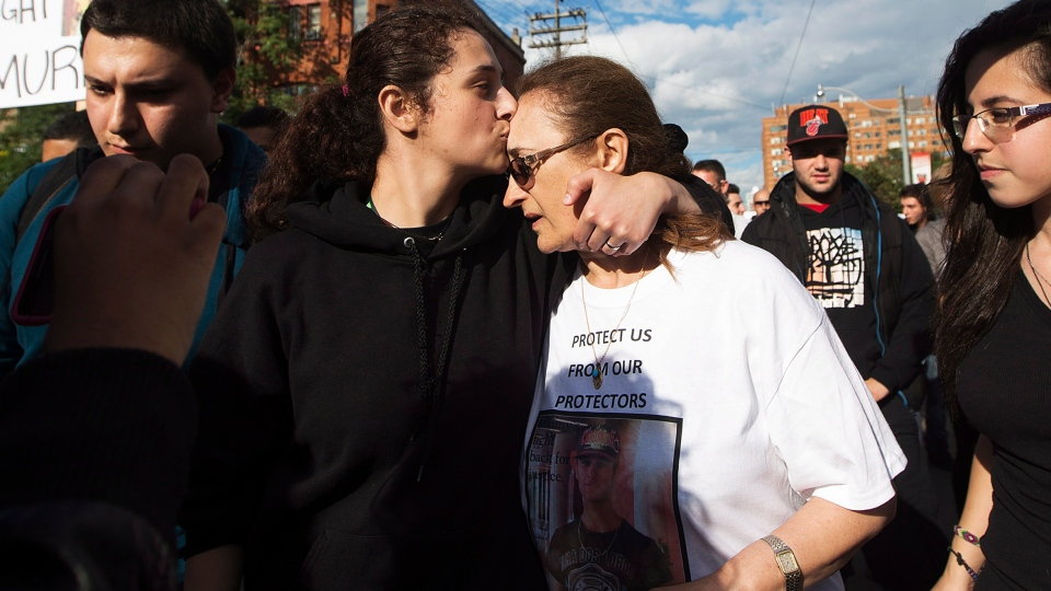 Mother Sahar Bahadi, right, is comforted by her daughter Sarah Yatim, left, as they march on Monday, July 29, 2013 to the spot where their son and brother Sammy Yatim was killed by police early Saturday morning in Toronto. (Michelle Siy / THE CANADIAN PRESS)