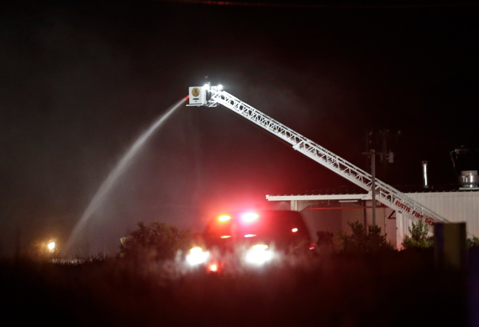 Fire crews pour water on a fire after an explosion at the Blue Rhino propane gas company Tuesday, July 30, 2013, in Tavares, Fla. (AP Photo/John Raoux)