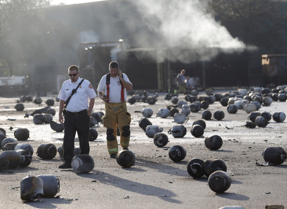 Firefighters walk through an area of exploded propane cylinders in the aftermath of an explosion and fire at a propane gas company in Tavares, Fla., Tuesday, July 30, 2013. (AP / John Raoux)