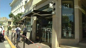 Police stand in front of Kronometry, a luxury watch retailer that was robbed in Cannes, France, Wednesday, July 31, 2013.
