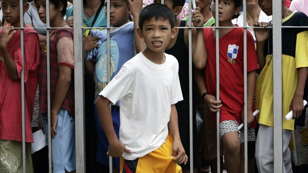 A newly circumcised boy walks past a line of other boys waiting to be circumcised during a free circumcision surgery Saturday, May 7, 2011, in Marikina city, east of Manila, Philippines. (AP Photo/Pat Roque)