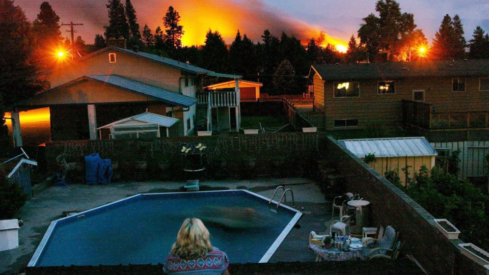 A resident watches the approaching flames in Kelowna, B.C. on Friday Aug. 22, 2003. (Rich Lam / THE CANADIAN PRESS)
