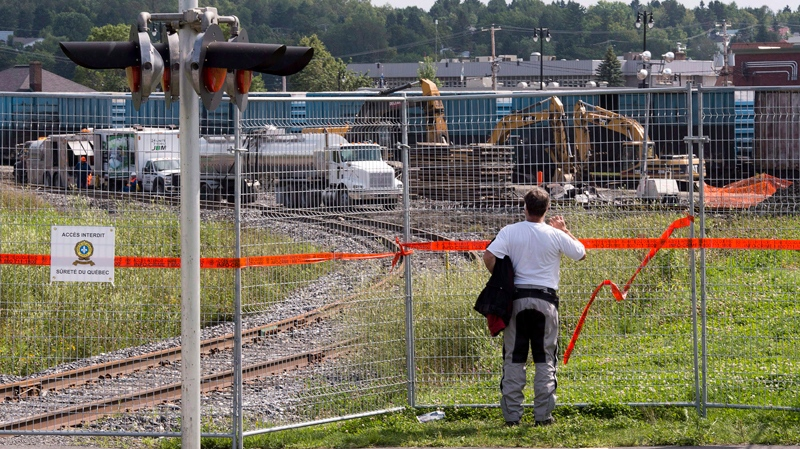 A man checks out the cleanup operations continuing in Lac-Megantic, Que., Wednesday, July 31, 2013. (Jacques Boissinot / THE CANADIAN PRESS)