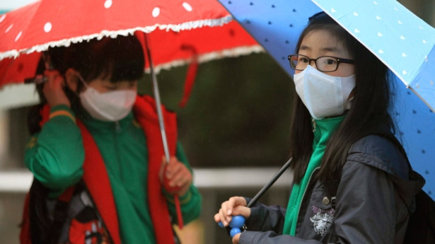 South Korean students holding umbrellas wait their friends to go to homes amid fears that the rain may contain radioactive materials from the crippled nuclear reactors in Japan at Midong elementary school in Seoul, South Korea, Thursday, April 7, 2011. (AP / Ahn Young-joon)