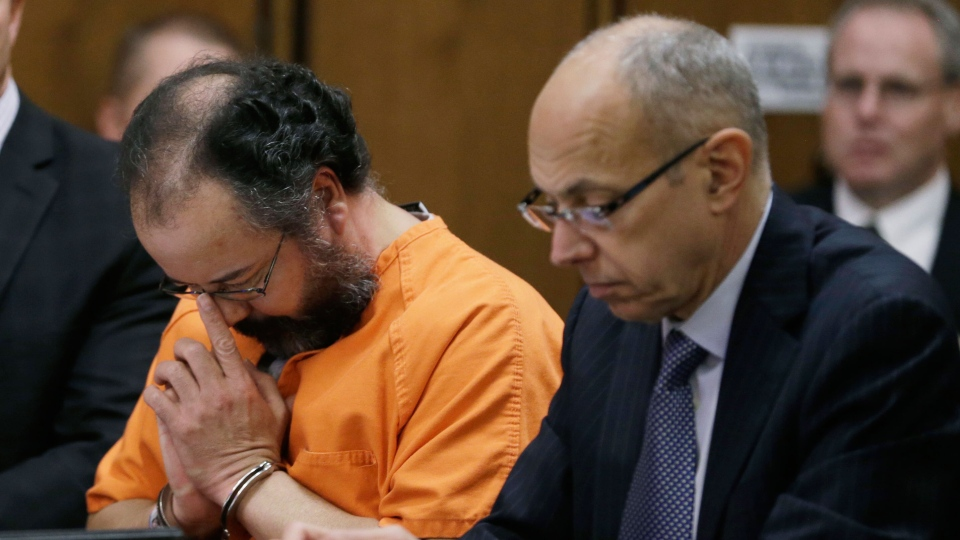 Ariel Castro, center, adjusts his glasses during the sentencing phase in Cleveland on Thursday, Aug. 1, 2013. (AP / Tony Dejak)