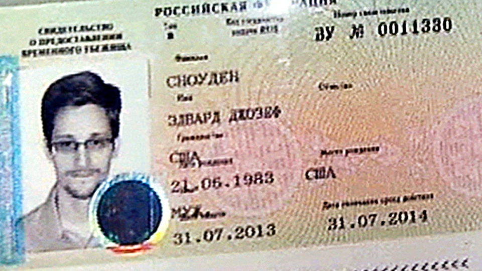 A copy of a temporary document to allow Edward Snowden to cross the border into Russia, held by Russian lawyer Anatoly Kucherena speaking to reporters after visiting Snowden at Sheremetyevo airport outside Moscow, Russia, on Thursday, Aug. 1, 2013.