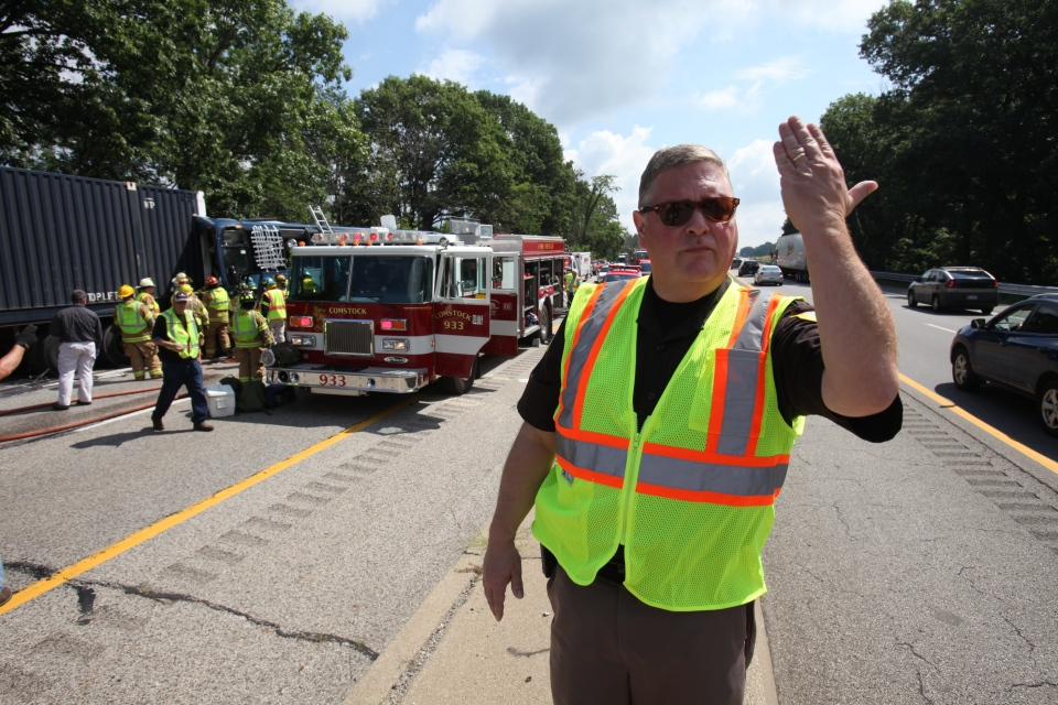 Kalamazoo County Sheriff Richard Fuller directs traffic in the eastbound lanes of I-94 to keep moving as emergency responders work to remove the bus driver from a Greyhound bus that collided with a semi- truck, on westbound Interstate 94 near Galesburg, Mich., Thursday, Aug. 1, 2013. (Kalamazoo Gazette-MLive Media Group)