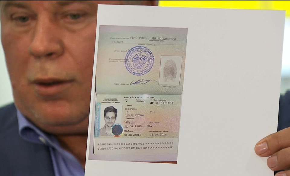 Russian lawyer Anatoly Kucherena holds a temporary document that allows Edward Snowden to cross the border into Russia at Sheremetyevo airport outside Moscow on Thursday, Aug. 1, 2013. (APTN)