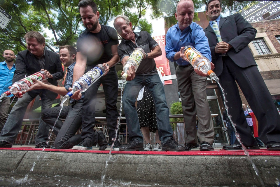 From left to right, Michael Niemeyer, Matthew Ervin, Alfredo Diaz, Richard Grossi, Rodney Scott and council member John Duran empty Russian vodka bottles into a gutter during a news conference in West Hollywood, Calif. on Thursday, Aug. 1, 2013. (AP / Ringo H.W. Chiu)
