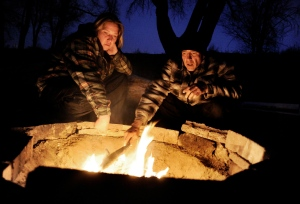 Shana Carlile, left, and Eloy Valverde warm themselves by a campfire in Colorado Springs, Colo., in this 2010 file photo. (The Denver Post / Craig F. Walker)