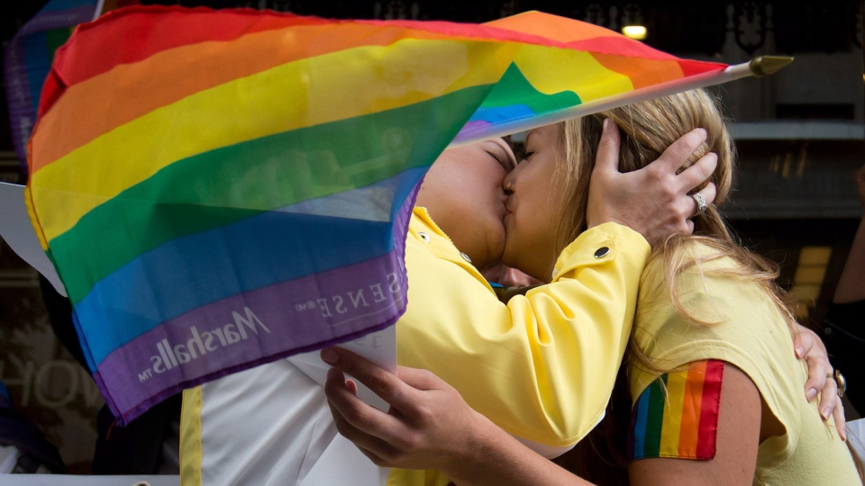Two women participate in a kiss-in outside the Russian Consulate to protest Russia's new anti-gay law in Vancouver, B.C., on Friday August 2, 2013. (Darryl Dyck / THE CANADIAN PRESS)