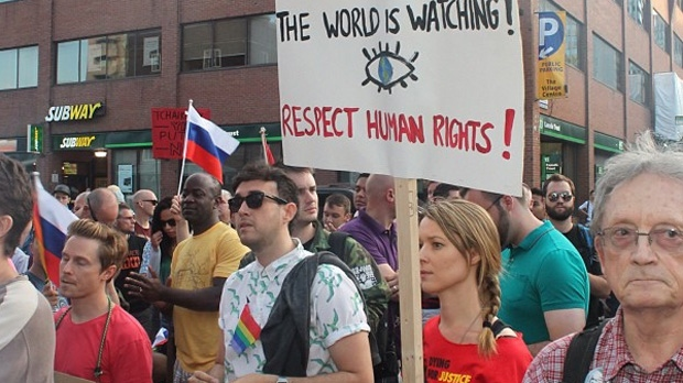 Protesters carry signs at Church and Wellesley streets in downtown Toronto to protest a new Russian law that criminalizes gay 'propaganda' Saturday August 3, 2013. (Mitchel Raphael)