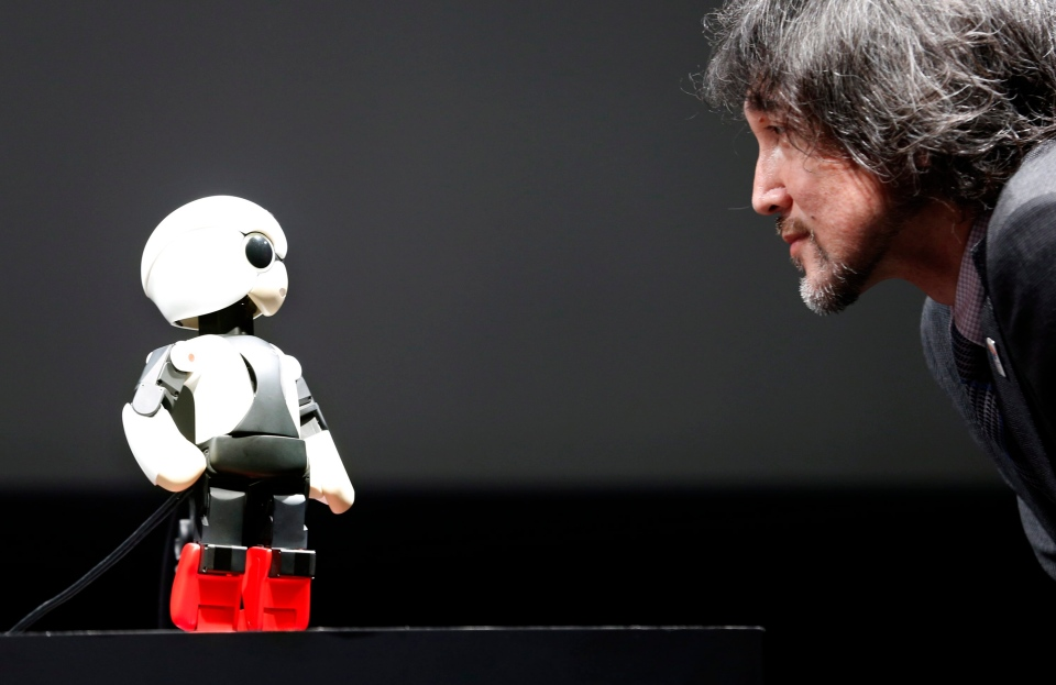 Humanoid communication robot Kirobo, left, talks with Fuminori Kataoka, project general manager from Toyota Motor Corp., during a press unveiling in Tokyo on June 26, 2013. (AP Photo/Shizuo Kambayashi)