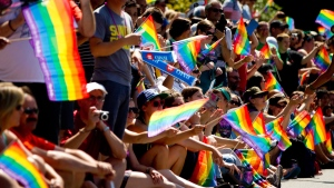 Spectators wave rainbow flags while attending the Vancouver Pride Parade in Vancouver, B.C., on Sunday August 4, 2013. (Darryl Dyck / THE CANADIAN PRESS)