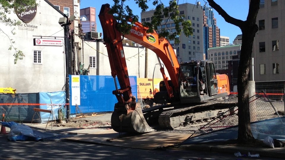 A backhoe is parked by a metal plate that dropped, killing a 32-year-old pedestrian in downtown Montreal on Monday, Aug. 5, 2013 (CTV Montreal/Jean-Luc Boulch)