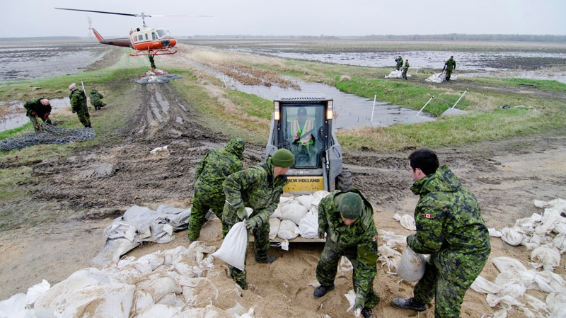Soldiers from the 2nd Battalion, Princess Patricia's Canadian Light Infantry (2 PPCLI) help load sandbags to be airlifted to the front lines of the fight against the rising Assiniboine River near Portage La Prairie, Manitoba Tuesday May 10, 2011. (David Lipnowski / THE CANADIAN PRESS)