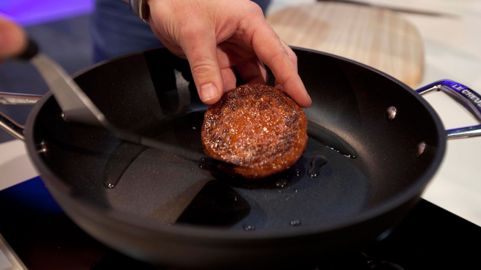 A new Cultured Beef Burger made from cultured beef grown in a laboratory from stem cells of cattle, is cooked by chef Richard McGeown during the world's first public tasting event for the food product held in London, Monday Aug. 5, 2013.  (AP / David Parry, PA)