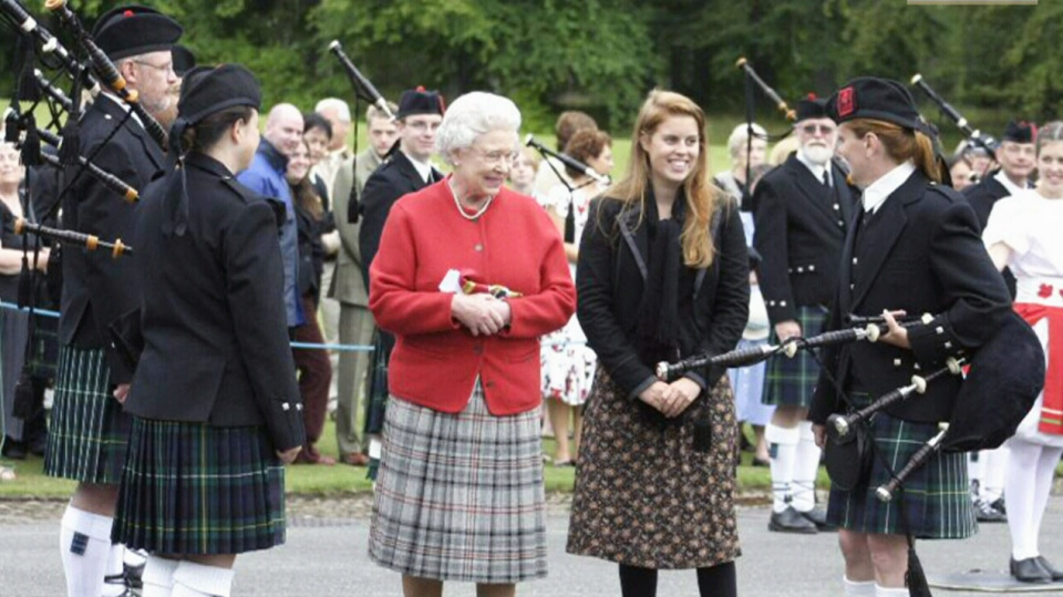 Queen Elizabeth II along with Bethany Bisaillion and members of the Sons of Scotland Pipe Band.