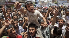 A Yemeni boy lifted by anti-government protestors, reacts during a demonstration demanding the resignation of Yemeni President Ali Abdullah Saleh, in Sanaa, Yemen, Tuesday, May 10, 2011. (AP Photo/Hani Mohammed)