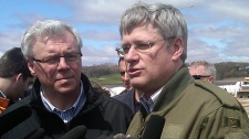 Manitoba Premier Greg Selinger (left) and Prime Minister Stephen Harper speak with media following a flood tour on May 11, 2011.