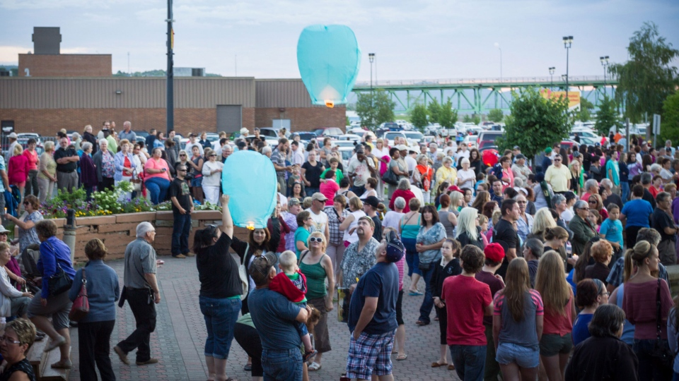 Mourners gather in Campbellton, N.B. to remember Noah and Connor Barthe on Wednesday, Aug. 7, 2013. (John LeBlanc / THE CANADIAN PRESS)