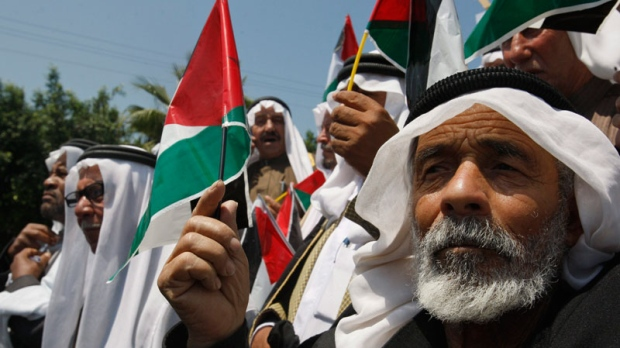 Palestinians wave flags as they celebrate the reconciliation between rival factions Fatah and Hamas, during a rally in Gaza City, Wednesday, May 11, 2011. (AP / Hatem Moussa)