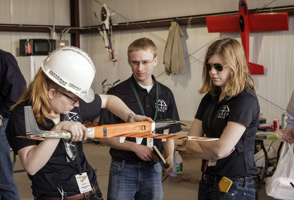 In this April 2013 photo provided by Oklahoma State University, Team Black members from left, Amelia Wilson, Nathan Woody and Alyssa Avery prepare their aircraft for flight during SpeedFest III at Oklahoma State University, in Stillwater, Okla. (AP Photo/ Oklahoma State University, Gary Lawson)