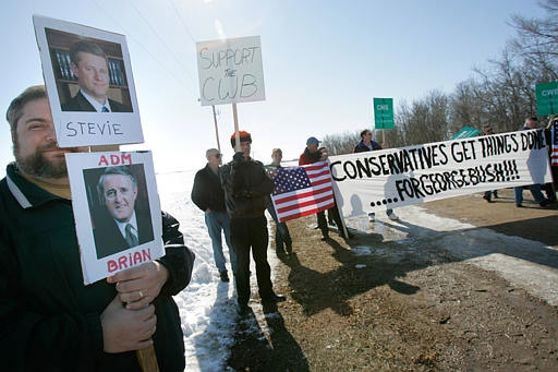 National Farmers Union member Grant Robertson, left, of Paisley, Ont., protests at the location of a news conference where Prime Minister Stephen Harper announced a one billion dollar commitment to national farm income programs in Saskatoon, Sask. Friday, March 9, 2007. (CP / Geoff Howe)