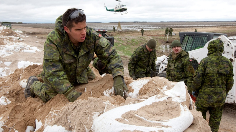 Members of 2nd battalion Princess Patricia's Light Infantry help load sandbags onto helicopter slings to be transported to weak sections of the dike running along the Assiniboine River some 25km from Portage La Prairie, Man. Thursday, May 12, 2011. (Jonathan Hayward / THE CANADIAN PRESS)