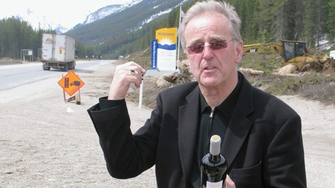 Radio host, former VJ and actor Terry David Mulligan speaks in front of the Alberta-B.C. border on the Trans-Canada Highway on Friday May 13, 2011. Mullligan carried across a case of B.C. wine to protest a law that prohibits the transport of liquor across provincial boundaries. May 13, 2011. (CP/Bill Graveland)