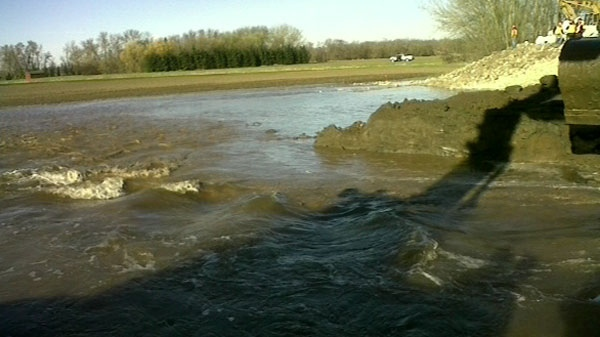 Water is seen flowing from the Assiniboine River, following the dike breach in Manitoba, Saturday, May 14, 2011. (Courtesy the government of Manitoba)