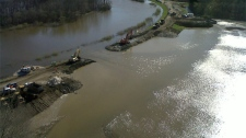 Water is seen flowing from the Assiniboine River, after a cut into a dike was made at Hoop and Holler Bend, southeast of Portage la Prairie, Man., Saturday, May 14, 2011. (Courtesy Government of Manitoba)