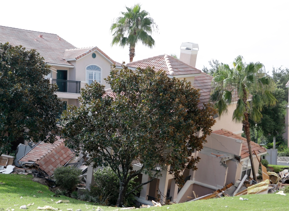 A portion of a building in Clermont, Fla., is shown in a sinkhole on Aug. 12, 2013. The sinkhole opened up overnight and damaged three buildings at the Summer Bay Resort. (AP / John Raoux)