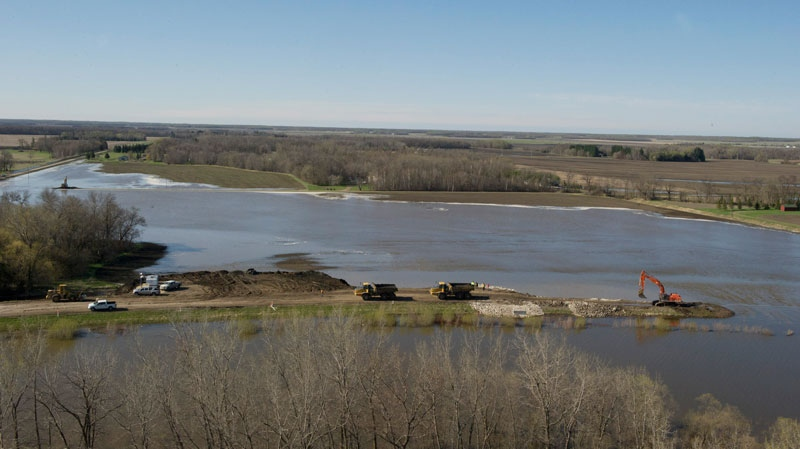 Water is seen flowing from the Assiniboine River, after a cut was made into a dike at Hoop and Holler Bend, southeast of Portage la Prairie, Man., Saturday, May 14, 2011. (Courtesy Government of Manitoba)