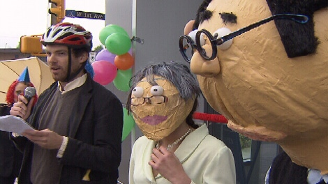 """Activists dressed like Vancouver Mayor Gregor Robertson, city manager Penny Ballem and """"Condo King"""" Bob Rennie hold a faux-press conference. Sunday, May 15, 2011. (CTV)"""