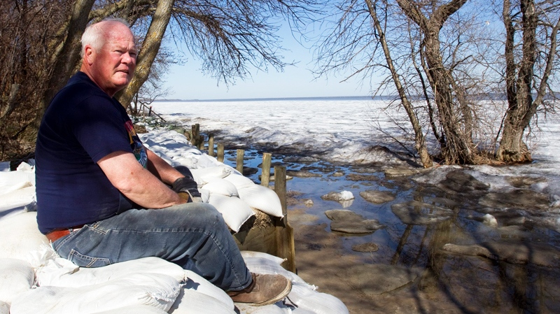 Retired school principal Larry Muirhead watches the rising waters of Lake Manitoba from his sandbagged backyard along the Assiniboine River in Delta Beach, Man., on Monday, May 16, 2011. (Ryan Remiorz / THE CANADIAN PRESS)