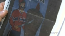 Fadl Issa holds a photo of the banner he had placed on the side of his building to support the Montreal Canadiens and which led to an $89,000 fine from the NHL