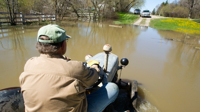 Robin Carter drives his tractor beside his home along the intentional breach of the dike along the Assiniboine River  in Manitoba on Monday, May 16, 2011. (Ryan Remiorz / THE CANADIAN PRESS)