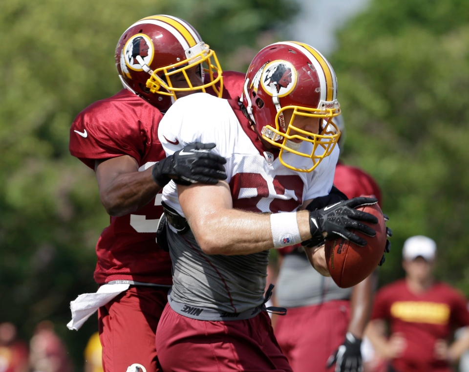 Washington Redskins running back Alfred Morris, front, grabs a pass in front of defensive back Jordan Pugh during the afternoon practice at the NFL football team's training camp in Richmond,Va., Friday, Aug. 2, 2013. (AP / Steve Helber)