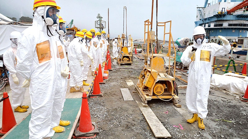 Officials and experts from local towns inspect a coastal embankment where contaminated water leaks occur near Fukushima Dai-ichi nuclear plant Unit 1 and 2 of Tokyo Electric Power Co., in Okuma, Fukushima prefecture, northeastern Japan, Aug. 6, 2013. (Kyodo News)